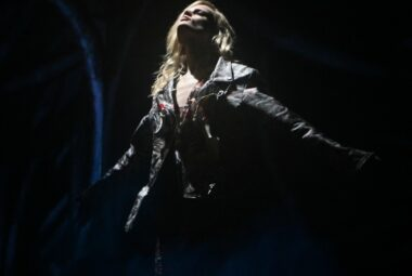 A woman leaning back in front of a spotlight