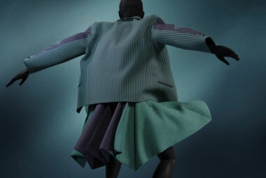 Dark virtual female model wearing striped jacket and a wide green skirt, while holding out her hands